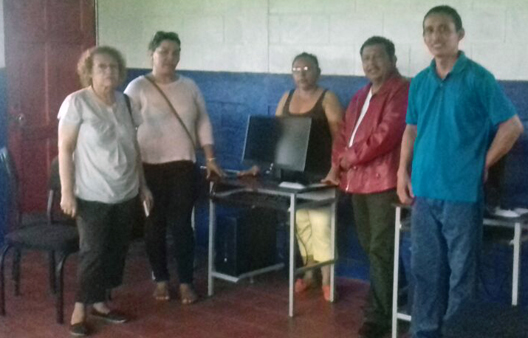 3 Rotarians from Chinandega making their official visit to La Carreta are shown with 2 of the teachers (woman in black blouse   and man in blue shirt).  Computer equipment, desks and chairs from the President's office can be seen in the photo taken in the   computer room.